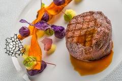 Εύγευστη μπριζόλα βόειου κρέατος με τη σάλτσα και το λαχανικό, που εξυπηρετούνται στο άσπρο πιάτο, τη σύγχρονη γαστρονομία, εστια στοκ φωτογραφίες με δικαίωμα ελεύθερης χρήσης
