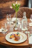 Εύγευστη μπριζόλα βόειου κρέατος με τη σάλτσα και το λαχανικό, που εξυπηρετούνται στο άσπρο πιάτο, τη σύγχρονη γαστρονομία, εστια στοκ φωτογραφία με δικαίωμα ελεύθερης χρήσης