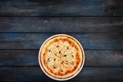 Εύγευστη πίτσα με τα μανιτάρια και κοτόπουλο σε μια ξύλινη στάση σε ένα σκοτεινό ξύλινο υπόβαθρο Τοπ κατώτατος προσανατολισμός άπ Στοκ φωτογραφία με δικαίωμα ελεύθερης χρήσης