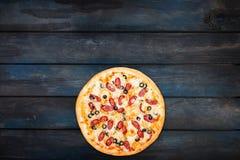 Εύγευστη πίτσα με το καπνισμένο λουκάνικο και ελιές σε ένα σκοτεινό ξύλινο υπόβαθρο Τοπ κατώτατος προσανατολισμός άποψης Στοκ φωτογραφία με δικαίωμα ελεύθερης χρήσης
