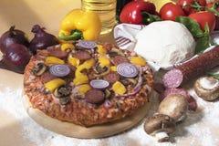 Εύγευστη πίτσα σε έναν ξύλινο πίνακα ντομάτα σαλαμιού πιτσών paprica συστατικών τυριών Στοκ φωτογραφίες με δικαίωμα ελεύθερης χρήσης