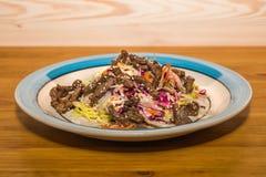 Εύγευστη σαλάτα των φρέσκων λαχανικών με τα καρυκεύματα σε ένα πιάτο στοκ εικόνα