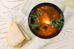 Εύγευστη σούπα saltwort σε ένα μαύρα κύπελλο και ένα ψωμί Στοκ Φωτογραφίες