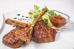 Εύγευστη σχάρα Ορεκτικά κομμάτια του ψημένου κρέατος στα κόκκαλα, χορτάρια και σάλτσα, σε ένα άσπρο πιάτο Οριζόντιο πλαίσιο Στοκ Φωτογραφίες