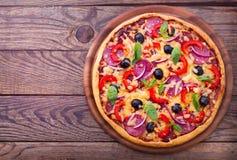 Εύγευστη φρέσκια πίτσα που εξυπηρετείται στον ξύλινο πίνακα. Στοκ Εικόνα