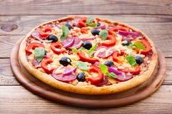 Εύγευστη φρέσκια πίτσα που εξυπηρετείται στον ξύλινο πίνακα. Στοκ εικόνες με δικαίωμα ελεύθερης χρήσης