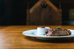 Εύγευστη ψημένη στη σχάρα μπριζόλα με το δεντρολίβανο και bbq σάλτσα στο πιάτο Στοκ φωτογραφία με δικαίωμα ελεύθερης χρήσης