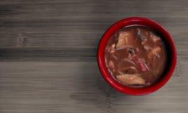 Εύγευστη bihuny σούπα σε ένα κόκκινο κύπελλο σε έναν πίνακα μπαμπού Στοκ εικόνες με δικαίωμα ελεύθερης χρήσης