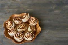 Εύγευστος και γλυκός που ψήθηκε αυξήθηκε διαμορφωμένη ζύμη με την πλήρωση μήλων στο ξύλινο διαμορφωμένο λουλούδι πιάτο στο ξύλινο Στοκ Εικόνες