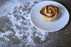 Εύγευστος και γλυκός που ψήθηκε αυξήθηκε διαμορφωμένη ζύμη με την πλήρωση μήλων στο άσπρο πιάτο στο ξύλινο υπόβαθρο που κονιοποιή Στοκ Εικόνα