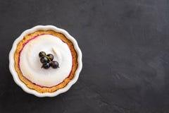 Εύγευστος ξινός που διακοσμείται με merengue και μούρα, που εξυπηρετούνται στην άσπρη αγροτική σύνθεση, με το διάστημα αντιγράφων στοκ εικόνες