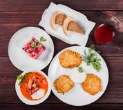 Εύγευστος πίνακας γευμάτων με τις τηγανίτες πατατών, παραδοσιακή σούπα παντζαριών - borscht με το βόειο κρέας, σαλάτα Vinaigrette στοκ φωτογραφία