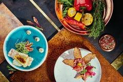 Εύγευστος σολομός tartare και κρέας tartare με το ψημένες ψωμί και τη σαλάτα σε ένα μπλε και άσπρο πιάτο σε ένα υπόβαθρο χαλκού στοκ εικόνες με δικαίωμα ελεύθερης χρήσης