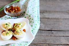 Εύγευστος τα αυγά σε ένα πιάτο Βρασμένα αυγά που γεμίζονται με το ξυμένο τυρί, τα μαριναρισμένα μανιτάρια και τα φρέσκα πράσινα κ Στοκ Φωτογραφία