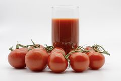 Εύγευστος χυμός ντοματών και ένα σύνολο χεριών των φρούτων στοκ εικόνα