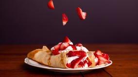 Εύγευστος crepes γεμισμένος με τις φράουλες και η κτυπημένη κρέμα με τις  φιλμ μικρού μήκους