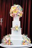 Εύγευστο άσπρο γαμήλιο κέικ πολυτέλειας που διακοσμείται με τα λουλούδια κρέμας Στοκ εικόνες με δικαίωμα ελεύθερης χρήσης