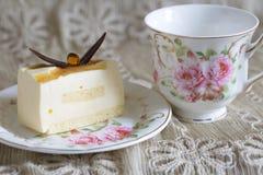 Εύγευστο άσπρο κέικ σοκολάτας και ένα όμορφο φλυτζάνι του τσαγιού για το θαυμάσιο πρωί στο μαλακό θολωμένο υπόβαθρο Στοκ Εικόνα