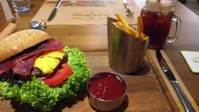 Εύγευστο ανοικτό burger που γεμίζουν με το μπέϊκον, το τυρί, τις ντομάτες, και το μαρούλι με το κέτσαπ και τα τηγανητά στην πλευρ φιλμ μικρού μήκους