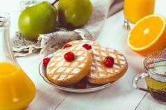 Εύγευστο, εύγευστο πρόγευμα: μπισκότα σε ένα πιάτο με τα φρούτα μούρων στον πίνακα Στοκ Φωτογραφία