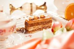 Εύγευστο κέικ με τα φυστίκια στο beautiflly διακοσμημένο πίνακα Στοκ φωτογραφία με δικαίωμα ελεύθερης χρήσης
