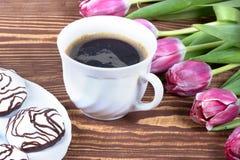 Εύγευστο κέικ με το coffe και τουλίπες στον πίνακα Στοκ εικόνα με δικαίωμα ελεύθερης χρήσης