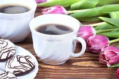 Εύγευστο κέικ με το coffe και τουλίπες στον πίνακα Στοκ φωτογραφία με δικαίωμα ελεύθερης χρήσης