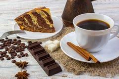 Εύγευστο κέικ σοκολάτας σε ένα πιάτο με ένα φλιτζάνι του καφέ Φασόλια καφέ, ένα κομμάτι των ραβδιών σοκολάτας, anice, ζάχαρης και Στοκ φωτογραφία με δικαίωμα ελεύθερης χρήσης