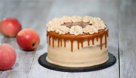 Εύγευστο κέικ το μήλο και την κτυπημένη πλήρωση κρέμας, που ολοκληρώνονται με με την καραμέλα στοκ εικόνα