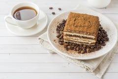 Εύγευστο κέικ Tiramisu με τα φασόλια καφέ σε ένα πιάτο και ένα φλυτζάνι ο στοκ φωτογραφίες