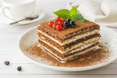 Εύγευστο κέικ Tiramisu με τα φρέσκα μούρα και μέντα σε ένα πιάτο σε ένα ελαφρύ υπόβαθρο Πρόγευμα με ένα φλιτζάνι του καφέ στοκ φωτογραφίες