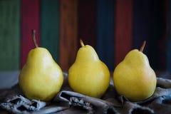 Εύγευστο κίτρινο αχλάδι Ουίλιαμς σε ένα ξύλινο υπόβαθρο των έγχρωμων ξύλινων πινάκων Απεικόνιση για τη διαφήμιση του χυμού αχλαδι στοκ εικόνες