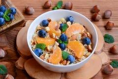 Εύγευστο και κουάκερ διατροφής με τα φρούτα, τα μούρα και τα καρύδια Κλασικό oatmeal με τα φρέσκες μανταρίνια, τα βακκίνια, τα φο στοκ εικόνα με δικαίωμα ελεύθερης χρήσης