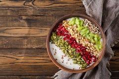 Εύγευστο και υγιές oatmeal με το ακτινίδιο, το ρόδι και τους σπόρους Στοκ Φωτογραφίες