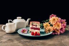 εύγευστο κομμάτι του κέικ με τα σμέουρα, τα όμορφες λουλούδια και την κατσαρόλα με την κανάτα πορσελάνης στοκ φωτογραφίες με δικαίωμα ελεύθερης χρήσης
