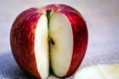 Εύγευστο κόκκινο μήλο δίπλα στις φέτες ενός άλλου μήλου στοκ εικόνες
