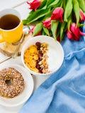 Εύγευστο κύπελλο γιαουρτιού με τις νιφάδες καλαμποκιού, τα καρύδια και τη μαρμελάδα σε έναν άσπρο ξύλινο πίνακα Υγιής και οργανικ στοκ εικόνες