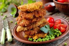 Εύγευστο μεσημεριανό γεύμα: χοιρινό κρέας που τηγανίζεται στο κτύπημα, τα μπιζέλια και τις ντομάτες κερασιών Στοκ Εικόνα