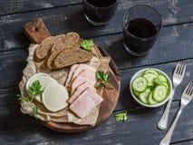 Εύγευστο ορεκτικό στο κρασί Καπνισμένο ζαμπόν, τυρί και δύο γυαλιά με το κόκκινο κρασί Στοκ Εικόνες