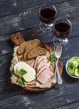Εύγευστο πρόχειρο φαγητό στο κρασί Καπνισμένο ζαμπόν, τυρί και δύο γυαλιά με το κόκκινο κρασί Στοκ Εικόνες