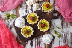 Εύγευστο σπιτικό λεμόνι ξινό Πίτα στον αγροτικό άσπρο πίνακα Ξινός με τα σμέουρα και τη μαρέγκα Στοκ Εικόνες