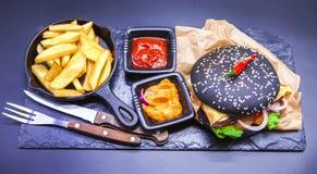 Εύγευστο σύνολο: burger, τηγανιτές πατάτες, σάλτσα κάρρυ, σάλτσα τσίλι, δίκρανο και μαχαίρι Στοκ Φωτογραφίες