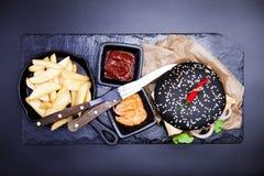 Εύγευστο σύνολο: burger, τηγανιτές πατάτες, σάλτσα κάρρυ, σάλτσα τσίλι, δίκρανο και μαχαίρι Στοκ φωτογραφία με δικαίωμα ελεύθερης χρήσης
