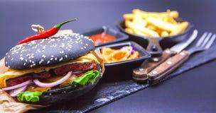 Εύγευστο σύνολο: burger, τηγανιτές πατάτες, σάλτσα κάρρυ, σάλτσα τσίλι, δίκρανο και μαχαίρι Στοκ Φωτογραφία