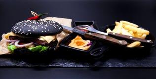Εύγευστο σύνολο: burger, τηγανιτές πατάτες, σάλτσα κάρρυ, σάλτσα τσίλι, δίκρανο και μαχαίρι Στοκ Εικόνα