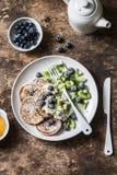 Εύγευστο υγιές πρόγευμα - ολόκληρες τηγανίτες σίτου με το ελληνικά γιαούρτι, τα βακκίνια, το ακτινίδιο, το μέλι και τα καρύδια σε στοκ εικόνες