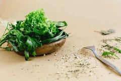 Εύγευστο φρέσκο σπανάκι arugula σαλάτας στο ξύλινα κύπελλο και τα μαχαιροπήρουνα Στοκ φωτογραφία με δικαίωμα ελεύθερης χρήσης