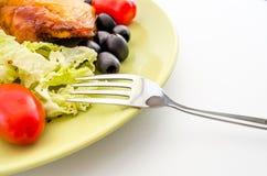 Εύγευστο ψημένο στη σχάρα κρέας που εξυπηρετείται σε ένα κίτρινο πιάτο με την ντομάτα και τις ελιές Στοκ εικόνα με δικαίωμα ελεύθερης χρήσης