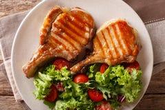 Εύγευστο ψημένο στη σχάρα μέλι χοιρινό κρέας μπριζολών που εξυπηρετείται με μια σαλάτα του φρέσκου β Στοκ Εικόνες