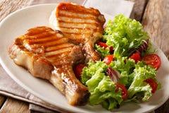 Εύγευστο ψημένο στη σχάρα μέλι χοιρινό κρέας μπριζολών που εξυπηρετείται με μια σαλάτα του φρέσκου β Στοκ φωτογραφία με δικαίωμα ελεύθερης χρήσης